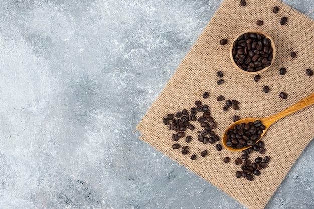 Деревянная ложка, полная жареных кофейных зерен на мешковине.