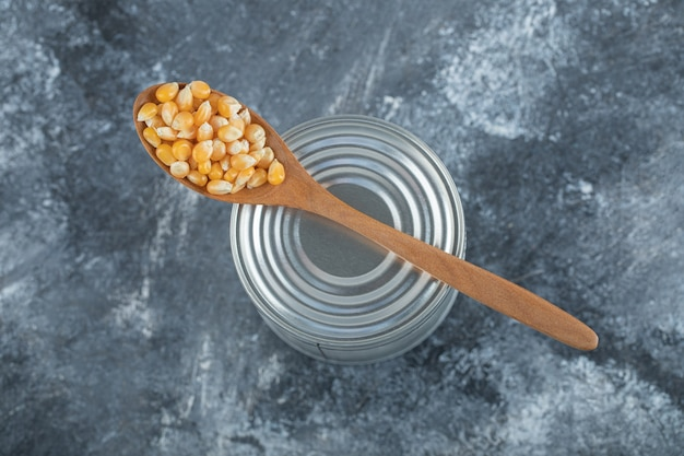 A wooden spoon full of popcorn seeds on marble.