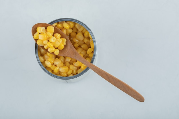 A wooden spoon full of popcorn seeds on white.