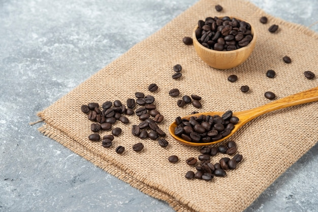 Wooden spoon full of roasted coffee beans on burlap.