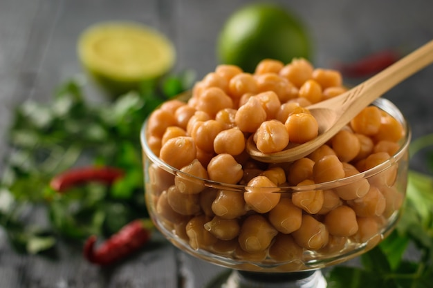 Wooden spoon in a glass bowl with boiled chickpeas with pepper and herbs