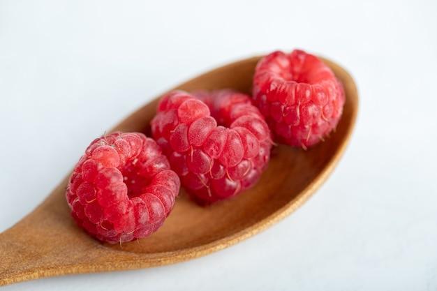 Wooden spoon of healthy ripe raspberries