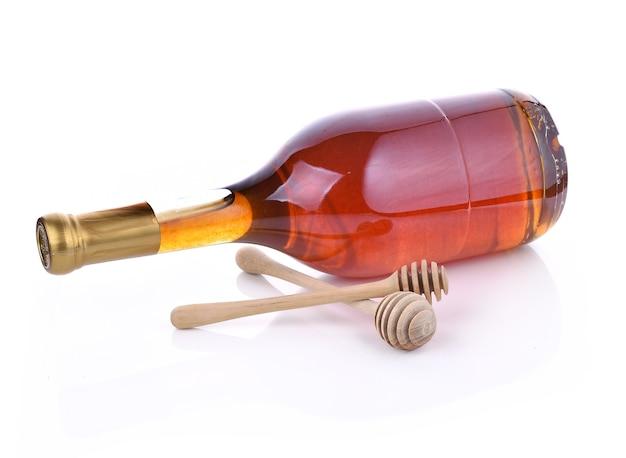 木製スプーン蜂蜜、白い背景の上の蜂蜜の瓶