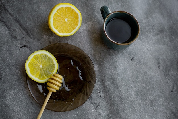 Wooden spoon of honey with lemon and black tea