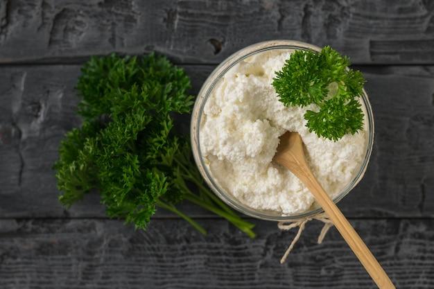 나무 테이블에 신선한 코 티 지 치즈와 함께 항아리에 나무 숟가락. 건강한 식단의 개념. 커드 크림. 상단에서보기.