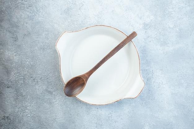 회색 표면에 빈 흰색 수프 접시에 나무 숟가락