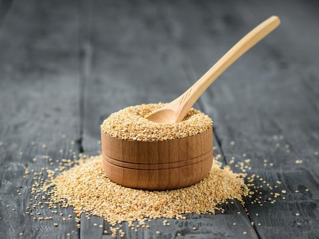 暗いテーブルにキノアの種子がいっぱい入った木製のボウルに軽い木で作られた木のスプーン。