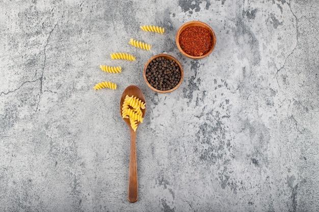 Деревянная ложка сырых макаронных изделий фузилли с различными специями перца на камне.