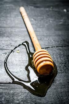 Деревянная ложка сладкого натурального меда. на черном деревенском столе.