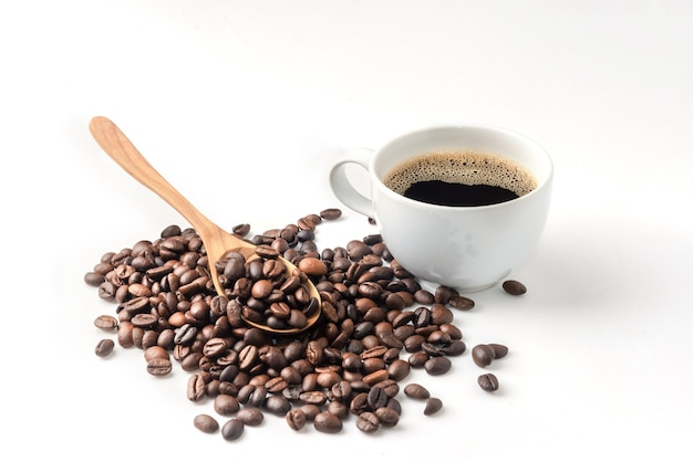 Деревянная ложка на кофейных зернах и чашка черного кофе на белом фоне
