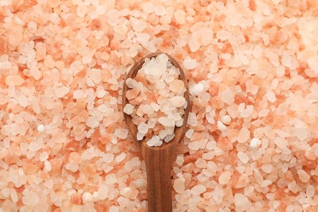 ピンクのヒマラヤの塩の背景に木のスプーン