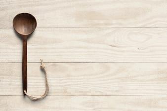 Wooden spoon on wooden bg