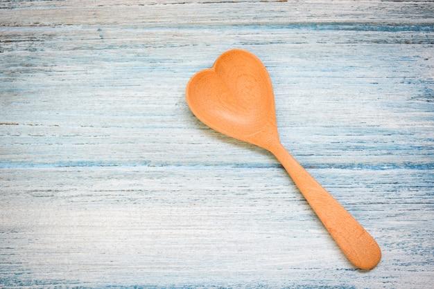 木製のテーブルの壁、トップビュー-コーヒースプーンハート形の木のスプーン、健康を愛する、または料理のコンセプトが大好き
