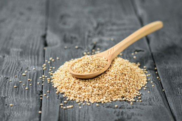 Wooden spoon in a pile of quinoa seeds on a dark wooden table