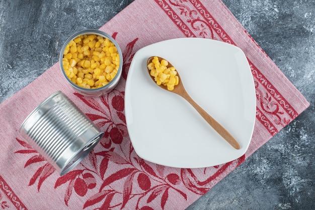 Un cucchiaio di legno di semi di popcorn su un piatto vuoto.