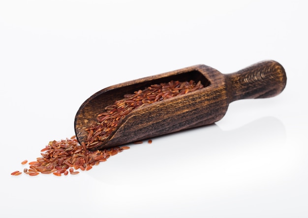 Wooden spoon of raw organic red rice on white table.