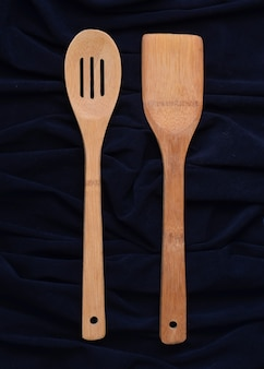 Wooden spoon and a spatula on a black background. top view.