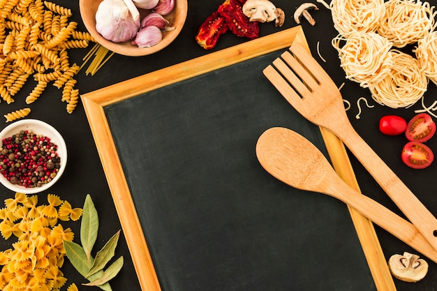Wooden spoon and spatula on slate surrounded with pasta ingredients