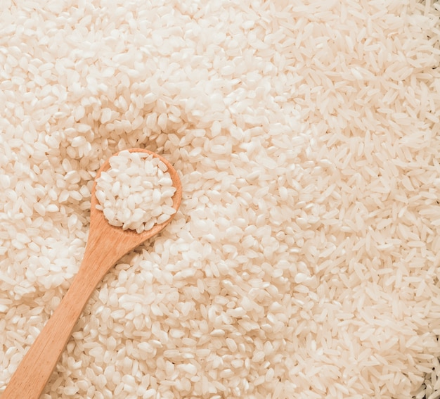 Wooden spoon in uncooked white rice grains