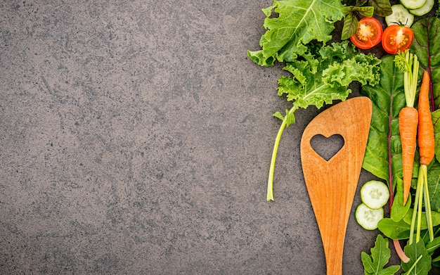 Wooden spoon and vegetables on dark stone background.
