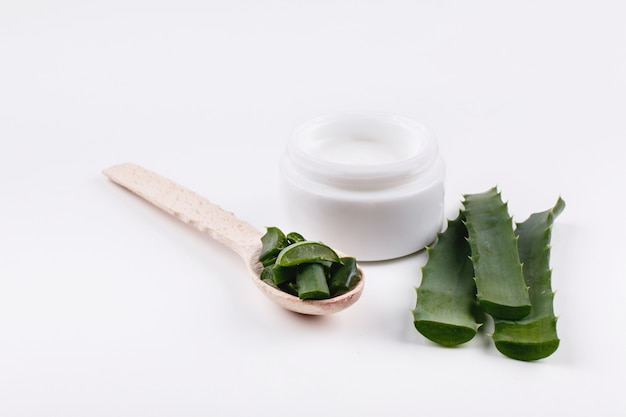 Wooden spoon with aloe lies on a white table with a bottle of white cream