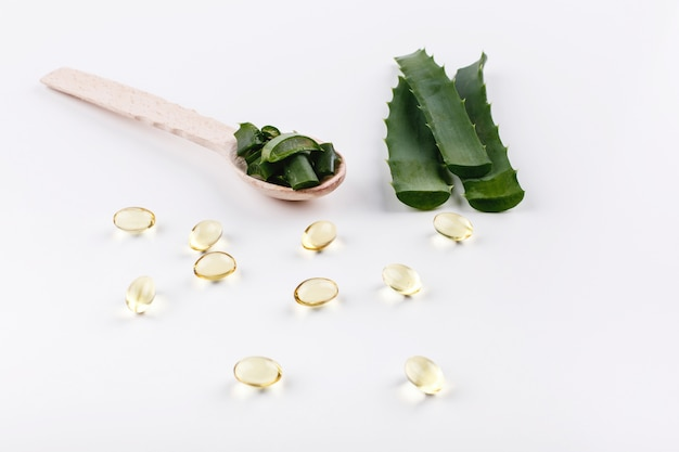 Wooden spoon with aloe lies on a white table with golden capsules with oil