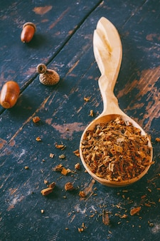 Wooden spoon with crushed oak bark for making infusion and acorns on old wooden black table