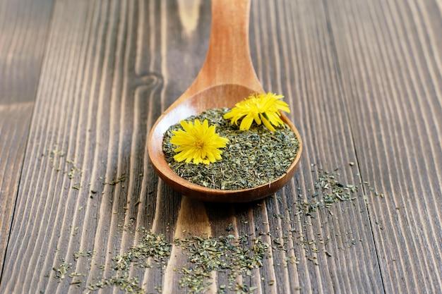 新鮮なタンポポの花と乾燥した茶葉と木のスプーンをクローズアップ。環境にやさしいオーガニックフラワーティー。