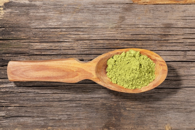 Wooden spoon with green matcha tea powder on wood. top view.