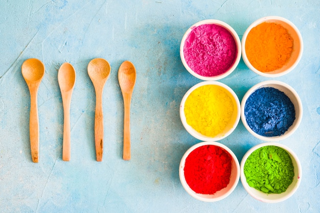 Wooden spoon with holi color powder in the white bowl on painted blue backdrop