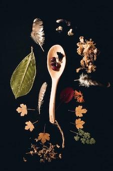 Cucchiaio di legno con foglie e piume su una tavola nera