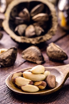 Деревянная ложка с множеством неочищенных орехов амазонки, также называемых акровыми орехами, боливийскими грецкими орехами, тори или турури.