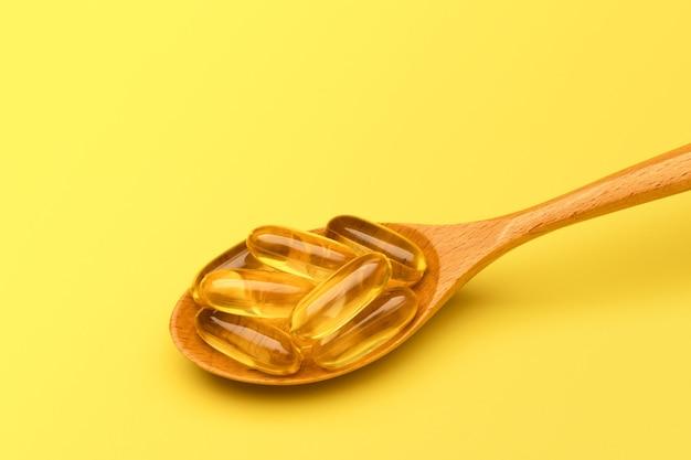 Деревянная ложка с таблетками омега-3 на желтой поверхности с копией пространства