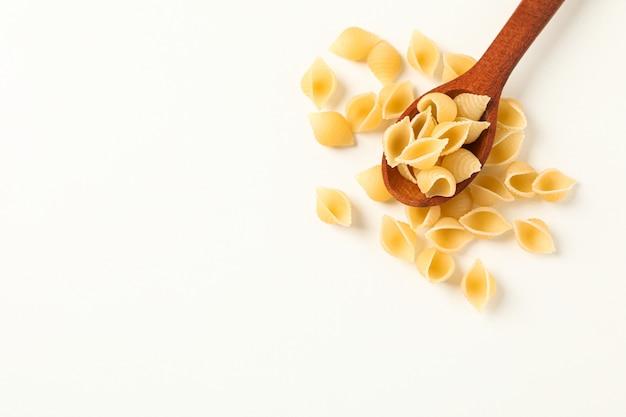 Деревянная ложка с макаронными изделиями на белой предпосылке, космосе для текста. сухие сырые целые макароны