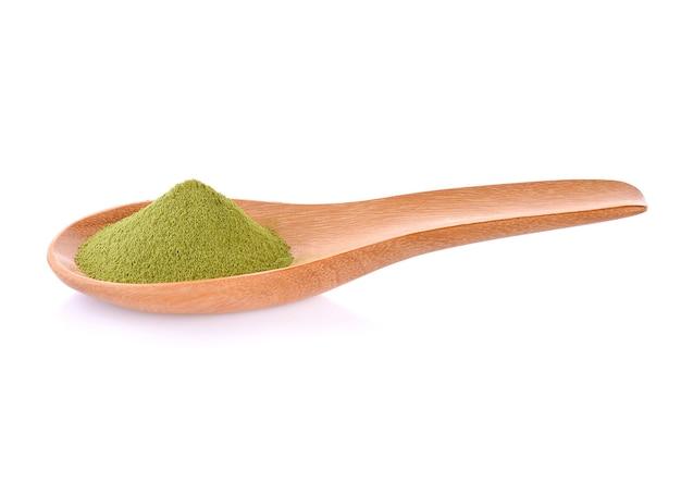 Деревянная ложка с напудренным зеленым чаем матча, изолированным на белизне; зеленый чай для здоровья.