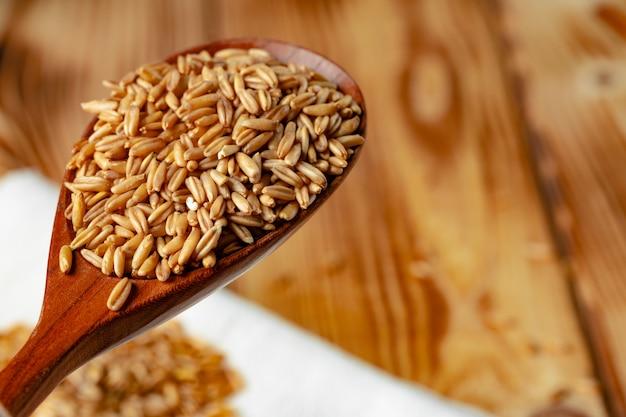 生のオート麦粒の木のスプーン