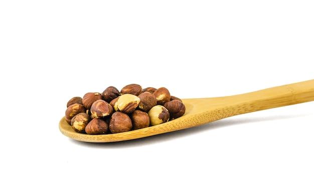 Деревянная ложка с жареным фундуком, изолированным на белой поверхности. готовится из урожая фундука.