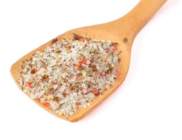 Wooden spoon with sea salt and a mixture of spices isolated on white.