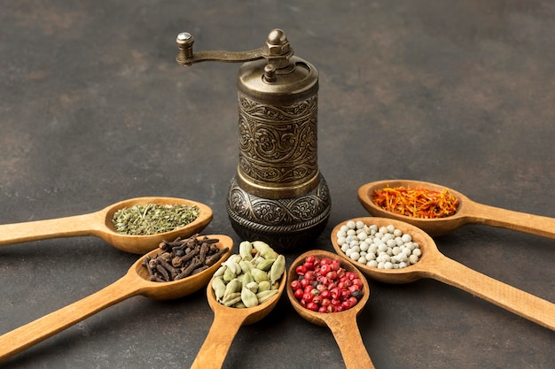 Wooden spoon with spices and grinder