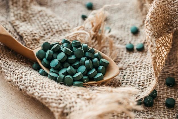 Деревянная ложка с таблетками спирулины на фоне мешковины