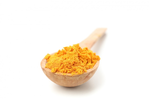 Wooden spoon with turmeric powder isolated on white