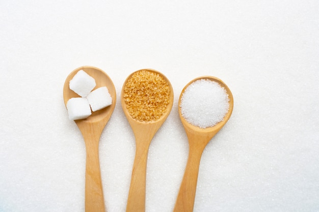 Wooden spoon with various types of sugar on white granulated sugar.