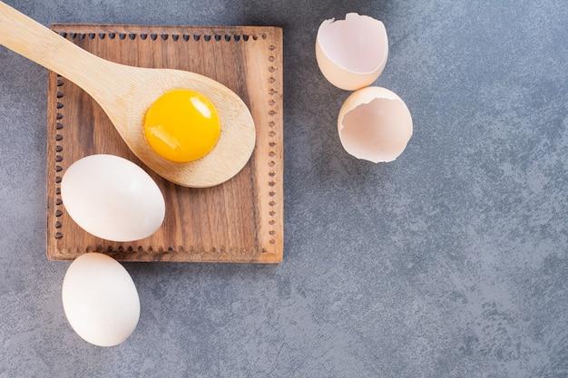 石のテーブルに卵黄と鶏の卵と木のスプーン。
