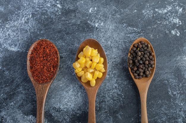 Cucchiai di legno di chicchi di mais, peperoni macinati e granella sulla superficie in marmo.
