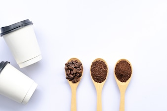 Wooden spoons filled with coffee bean and crushed ground coffee