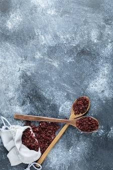 Un cucchiaio di legno pieno di mirtilli rossi organici sulla superficie di marmo.