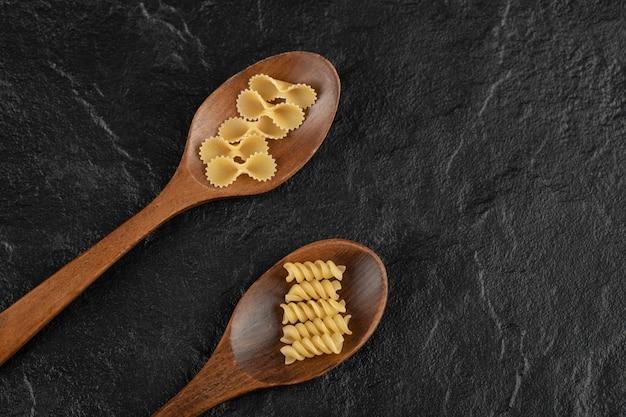 Cucchiai di legno pieni di girandole crude e farfalle tonde.
