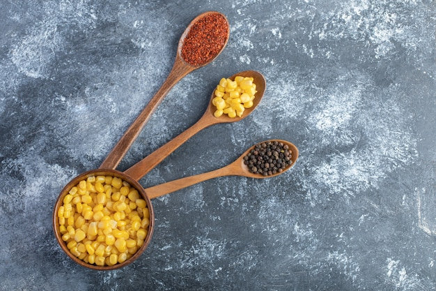 Wooden spoons of ground and grain peppers with bowl of corns.