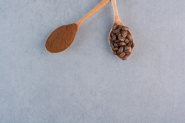 Wooden spoons of ground and roasted coffee beans on stone background.