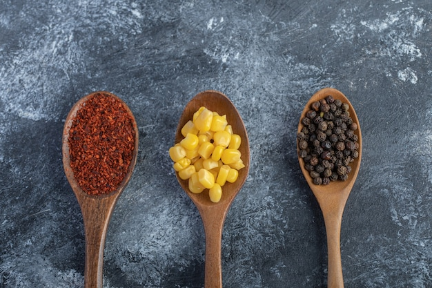 Деревянные ложки кукурузных зерен, молотого и зернового перца на мраморной поверхности.